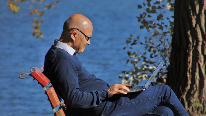 Man sitting on park bench with laptop near the water
